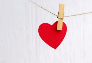 red heart hanging on wooden background